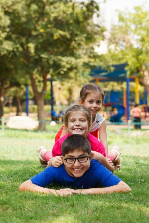 Photo for Happy children of three playing piggy back, looking at the camera. - Royalty Free Image