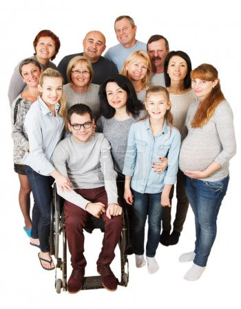 Foto de Portrait of a large group of a Mixed Age people smiling and embracing together with Disabled Man. - Imagen libre de derechos