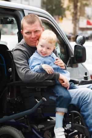 Photo pour Garçon de 4 ans et hommes handicapés de 35 ans sur ascenseur en fauteuil roulant - image libre de droit
