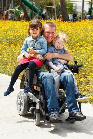 Photo pour Désactivé le père jouer avec son petit fils et fille - image libre de droit