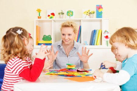 Photo for Preschool: Young smiling teacher discussing with group of children. Learning and having fun. Selective focus to teacher talking. - Royalty Free Image