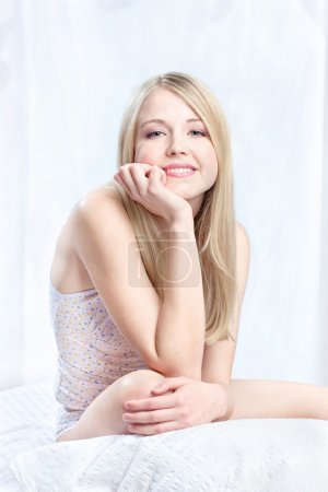 Photo for Blond woman sitting on bed - Royalty Free Image