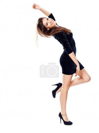 Photo pour Femme heureuse en robe noire sur les talons d'une main vers le haut, isolé - image libre de droit