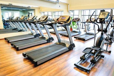 Photo pour Ensemble de tapis de course restant en ligne dans la salle de gym - image libre de droit