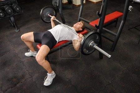Photo pour Beau jeune homme couché entraînement réside dans la salle de gym - image libre de droit