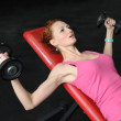 Young girl doing Dumbbell Incline Bench Press workout in gym