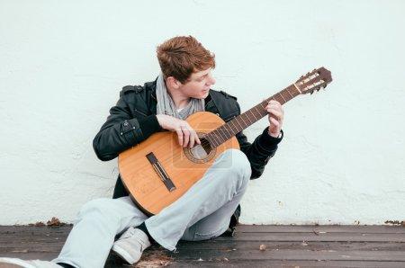 Photo pour Beau jeune homme jouant de la guitare acoustique - image libre de droit