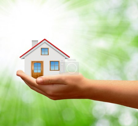 Photo pour La maison dans les mains sur vert naturel backgorund - image libre de droit