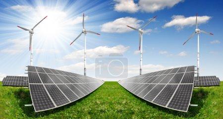 Foto de Paneles de energía solar con las turbinas de viento en el cielo azul - Imagen libre de derechos