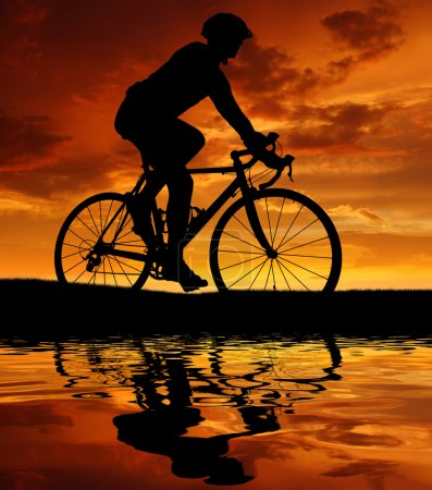 Photo for Silhouette of the cyclist riding a road bike at sunset - Royalty Free Image