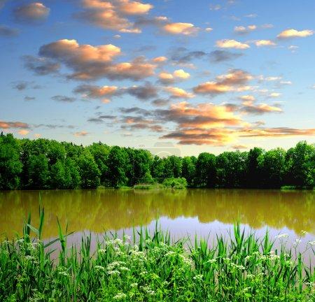 Puesta de sol sobre el paisaje primaveral con estanque - República Checa