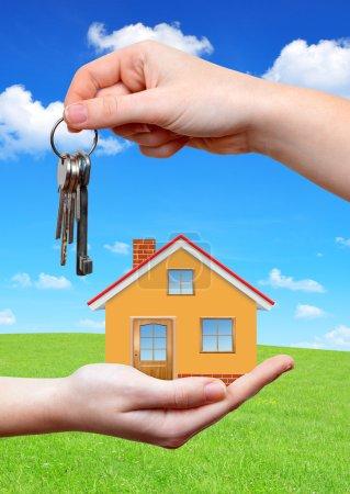Photo pour La maison avec la clé dans les mains sur le fond prairie de printemps - image libre de droit