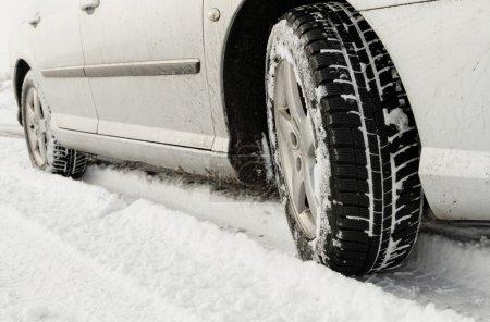Photo pour Gros plan d'un pneus de voitures sur une route enneigée - image libre de droit