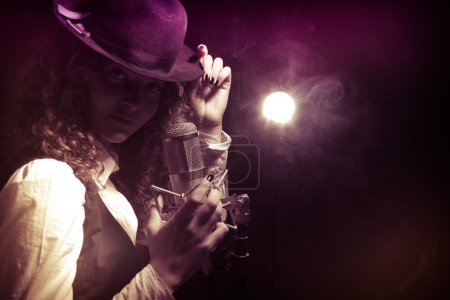 Beautiful singer in hat with microphone