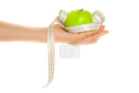 Photo pour Main de femme avec pomme verte et ruban à mesurer isolé sur blanc - image libre de droit