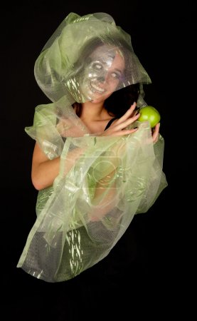 Two-faced woman with green apple smiling