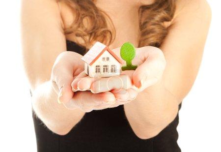 Photo pour Mains de femme tenant une maison et un toi - image libre de droit