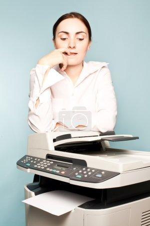 Businesswoman with copier thinking
