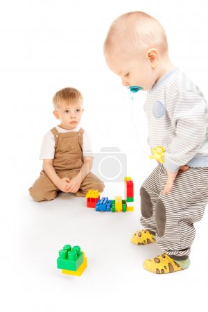 Photo for Two beautiful children playing with blocks in studio - Royalty Free Image