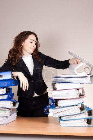 Photo for Stressed businesswoman with stack of folders at office - Royalty Free Image