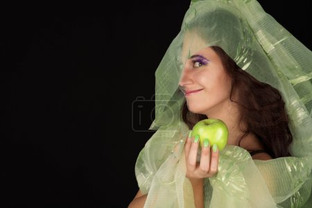 Cunning witch with green apple smiling