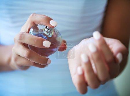 Photo pour Femme appliquant le parfum sur son poignet, bouteille de parfum rouge vif - image libre de droit