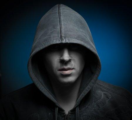 Photo pour Effrayant homme maléfique avec capuche dans les ténèbres - image libre de droit