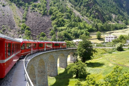 Photo for Swiss mountain train Bernina Express passes the spiral of the Brusio Viaduct - Royalty Free Image