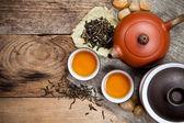 čajové šálky s konvici na starý dřevěný stůl