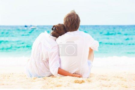 Photo pour Vue arrière du jeune couple heureux assis sur la plage tropicale. concept de lune de miel - image libre de droit