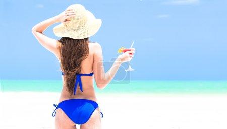Woman in straw hat and bikini enjoying cocktail on beach