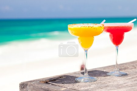 Two perfect mango and strawberry margarita, beach background