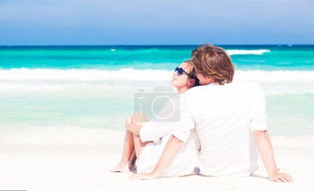 Young happy couple in white having fun on the beach