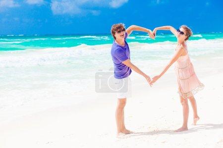 Young happy couple on honeymoon making heart shape on tropical beach