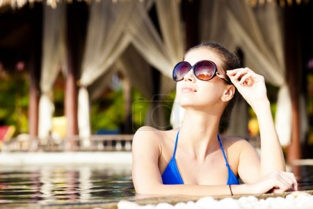 Beautiful young woman in sunglasses with flower in hair smiling in luxury pool