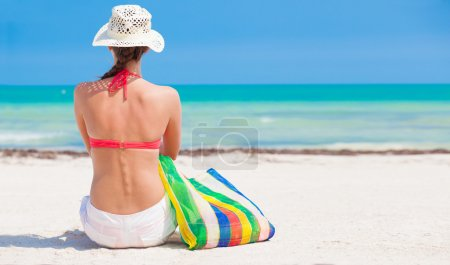 Woman in bikini and straw hat with beach bag sitting on beach. back view
