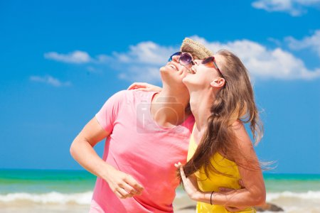 Closeup of happy young couple in sunglasses on beach smiling and looking at sky