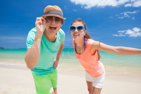 Portrait of happy young couple in bright clothes and sunglasses having fun on tropical beach