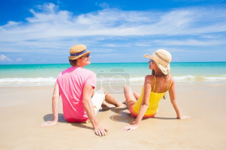 happy young couple having in straw hats sitting on tropical beach