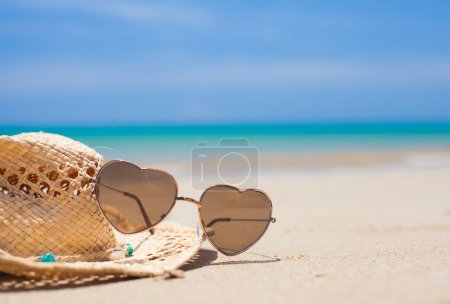 heart shaped sunglasses and straw hat on tropical beach