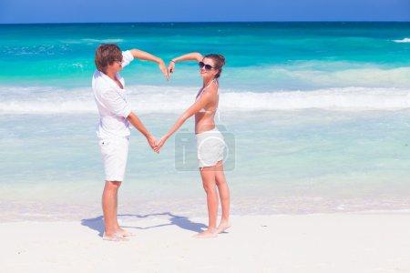 young happy couple making heart shape on tropical beach. honeymoon