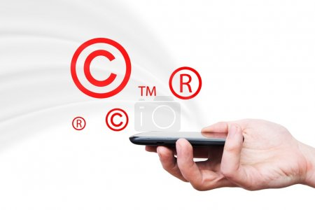 Copyright, trademark symbols flying from smartphone. Security and piracy composition