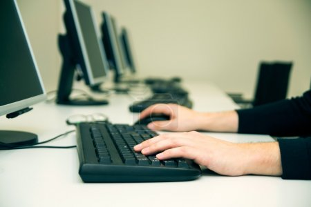 Photo pour Jeune homme tapant sur le clavier. Salle de formation avec ordinateurs - image libre de droit