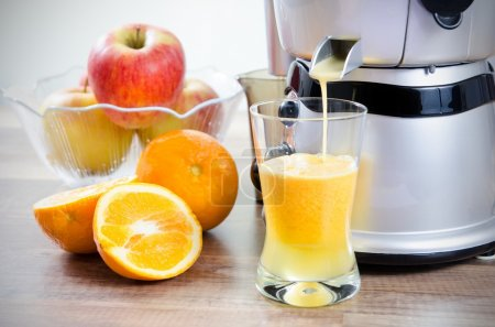 Photo for Juicer and orange juice. Fruits in background - Royalty Free Image