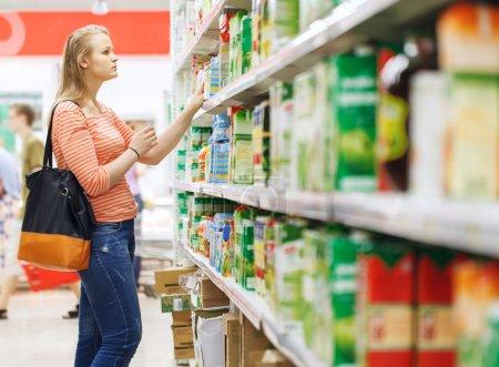 Photo pour Jeune femme shopping pour jus dans le département et les produits d'un supermarché - image libre de droit