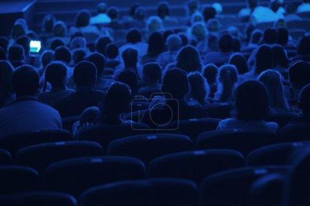 Photo pour Public au cinéma. Silhouette prise de dos à la lumière bleue . - image libre de droit