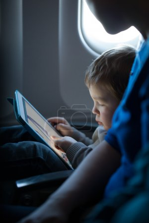 Little boy playing with a tablet in an airplane