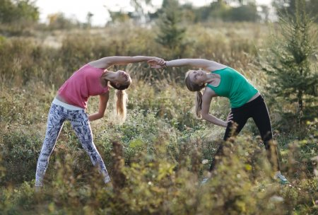 Two supple young women working out together
