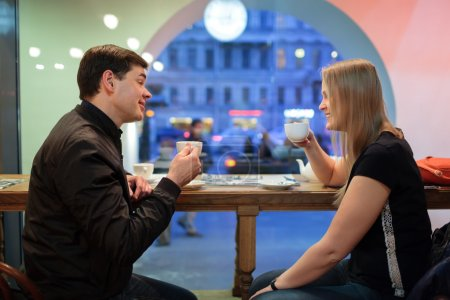 Photo for Man and woman chatting over a cup of coffee inside a cafe or restaurant - Royalty Free Image