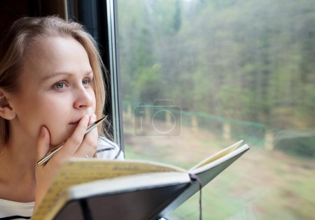 Photo for Young woman on a train writing notes in a diary or journal staring thoughtfully out of the window with her pen to her lips as she thinks of what to write - Royalty Free Image